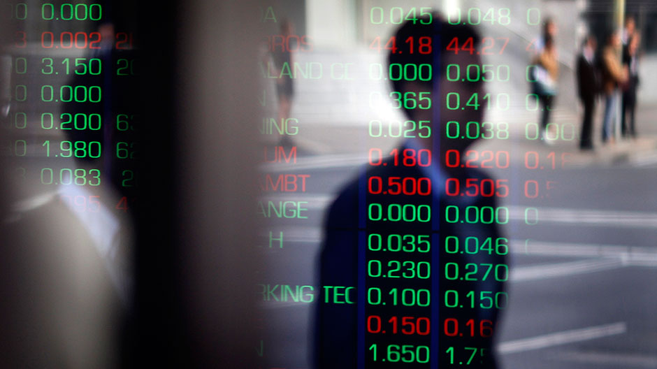 A man is reflected in a window as he walks past the indicator boards at the Australian Stock Exchange in Sydney August 11, 2011.
