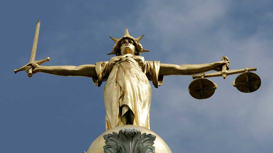 The Statue of Justice, depicted as a women with a sword in one hand and scale in her other, is seen on top of the London Central Criminal Court, the Old Bailey in London August 12, 2005.